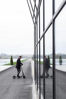 Volwassen mannetje poseren met zijn elektrische scooter