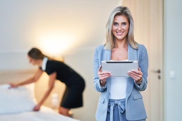 Volwassen meid en hotelmanager die de kamer schoonmaakt