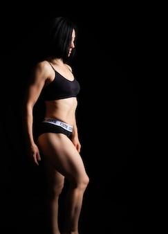 Volwassen meisje met een sport figuur in zwarte beha en zwarte korte broek staan