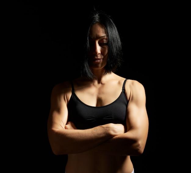 Volwassen meisje met een sportcijfer in zwarte bustehouder en zwarte borrels die zich op een donkere achtergrond bevinden