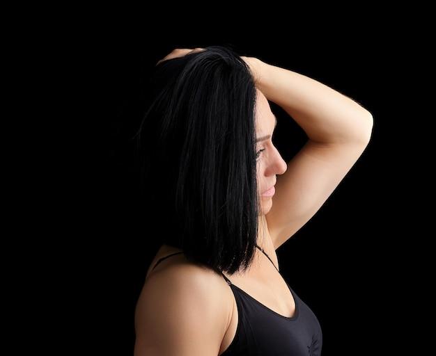 Volwassen meisje met een sportencijfer in zwarte bustehouder die zich op dark bevinden