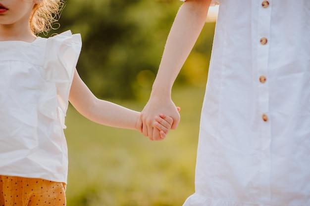 Volwassen meisje met zussen hand in een park vrienden concept