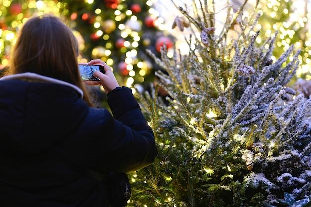 Volwassen meisje neemt een foto op haar telefoon van een kerstboom versierd met slingers met gloeiende lichten 's nachts, achteraanzicht