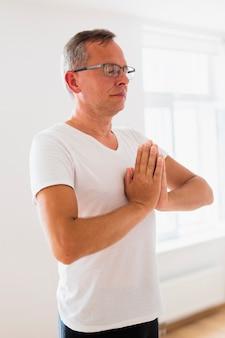 Volwassen mens die bij yogastudio mediteren