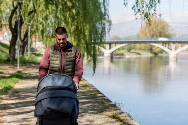 Volwassen mens die met babywandelwagen dichtbij rivier loopt