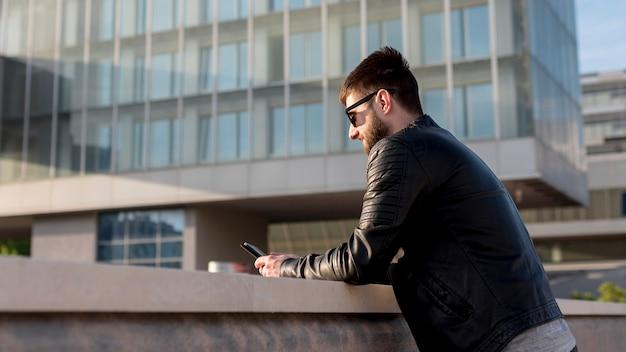 Volwassen mens die mobiele telefoon buiten met behulp van tijdens zonsondergang