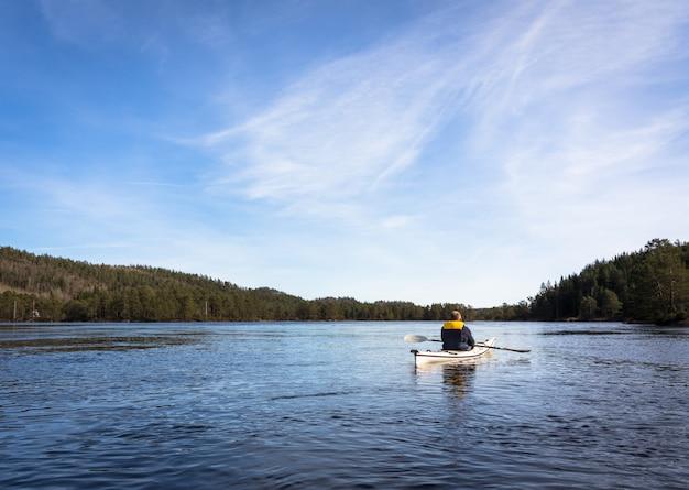 Volwassen mens die noorse rivier in witte kajak in nidelva peddelen, noorwegen