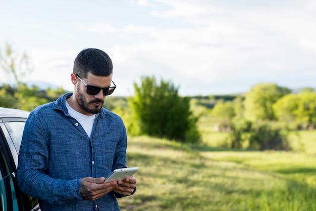 Volwassen mens die op auto leunt en tablet gebruikt