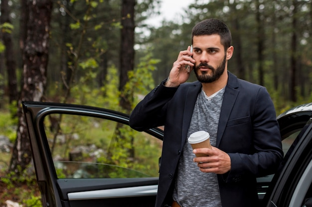 Volwassen mens die op telefoon dichtbij geopende autodeur spreekt
