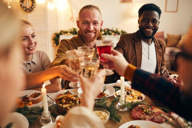 Volwassen mensen verhogen glazen op dinner party