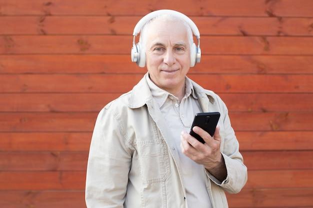 Volwassen mode man plezier met nieuwe trends technologie. trendy senior man met smartphone app met rode achtergrond. technologie en vreugdevolle ouderen levensstijl concept