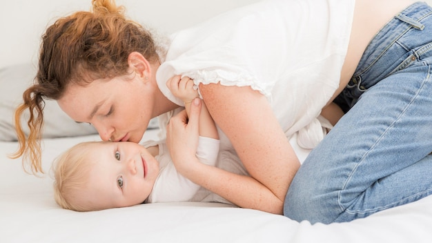 Volwassen moeder die haar babymeisje kust