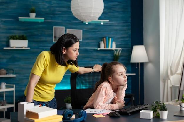Volwassen moeder kijkt naar klein meisje dat schoolwerk doet