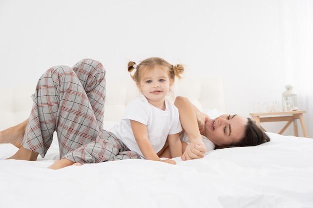Volwassen moeder speelt thuis met kleine actieve dochters, heeft plezier, vrijetijdsbesteding met kinderen.