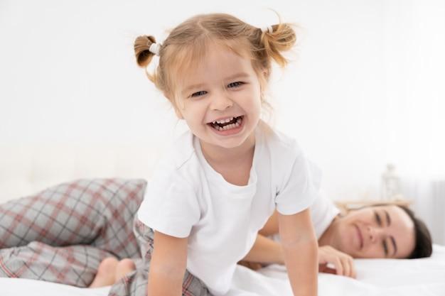 Volwassen moeder spelen met actieve dochtertje in bed thuis, met plezier, activiteit met kinderen.