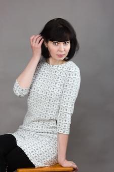Volwassen mooi vrouwenmodel op houten stoel dichtbij grijze achtergrond