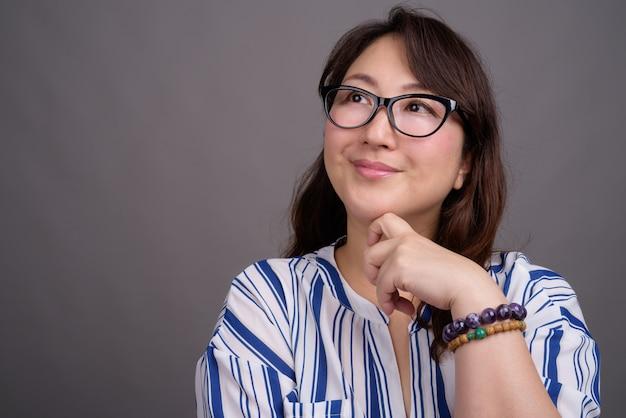 Volwassen mooie aziatische zakenvrouw draagt een bril