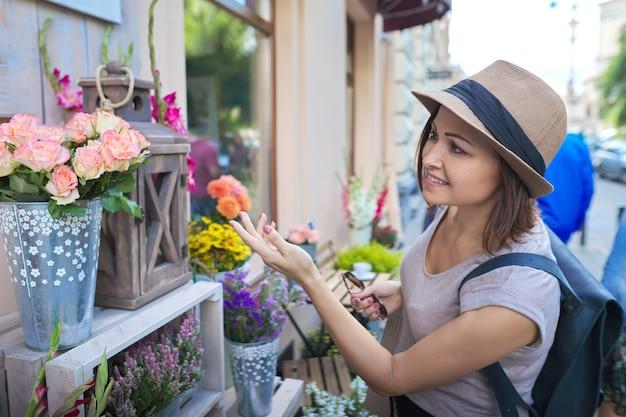 Volwassen mooie lachende vrouw met boodschappentassen bloemen kiezen bij openlucht bloemenwinkel.