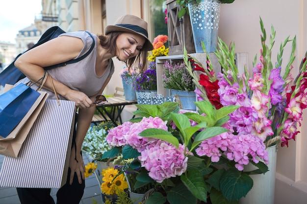 Volwassen mooie lachende vrouw met boodschappentassen bloemen kiezen bij openlucht bloemenwinkel