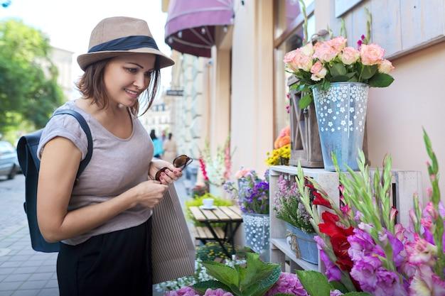 Volwassen mooie lachende vrouw met boodschappentassen bloemen kiezen