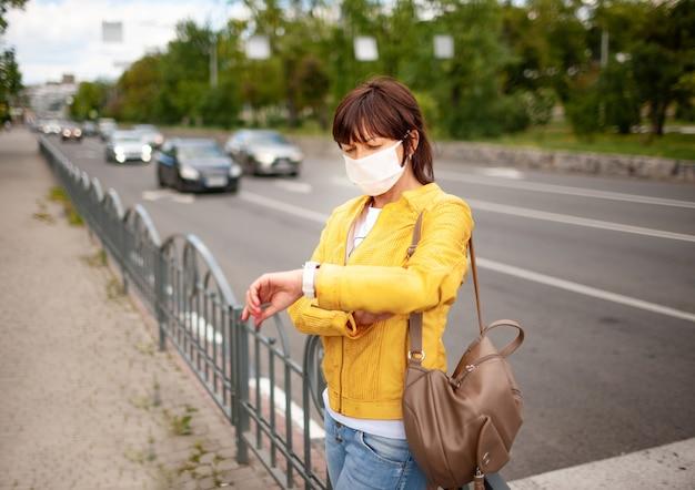 Volwassen mooie vrouw in vrijetijdskleding en tas met een beschermend masker op haar gezicht