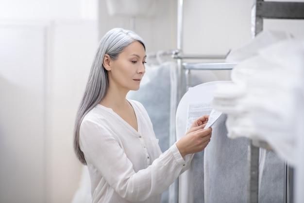 Volwassen mooie vrouw met lang grijs haar die informatie over kledinglabel bestudeert voor het geval dat op hanger hangt
