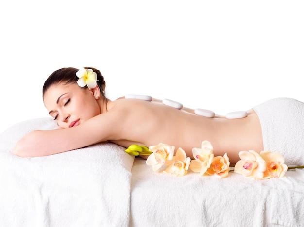 Volwassen mooie vrouw ontspannen in spa salon met hete stenen op rug