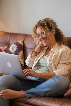 Volwassen mooie vrouwelijke mensen kijken naar de inhoud van de internetcomputer, liggen en ontspannen op de bank thuis - vrouw glimlacht naar een display en geniet van een alternatieve baan en werklevensstijl - dame met een bril