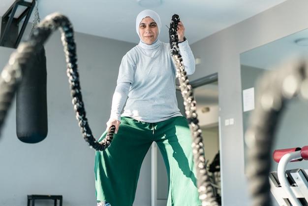 Volwassen moslimvrouw met behulp van touwen in de sportschool