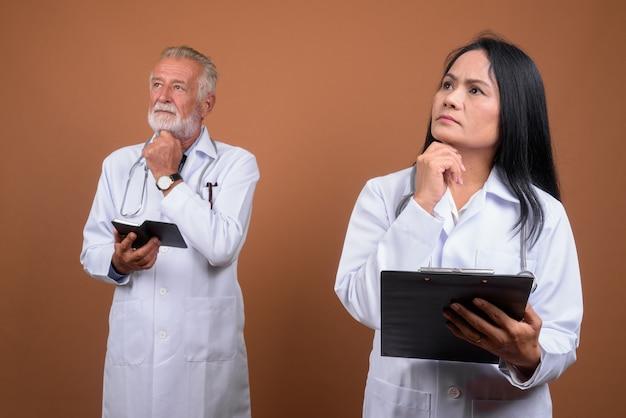 Volwassen multi-etnische paar artsen op bruin