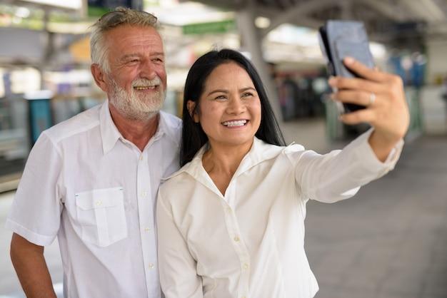 Volwassen multi-etnische paar gelukkig en verliefd tijdens het verkennen van de stad bangkok