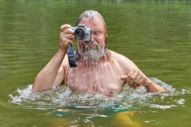 Volwassen natte bebaarde man met waterdichte camera in zijn handen is zwemmen in de rivier en fotograferen tijdens zijn vakantie.