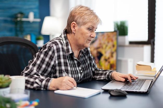 Volwassen ondernemer die aantekeningen maakt op een notebook die in een thuiskantoor werkt