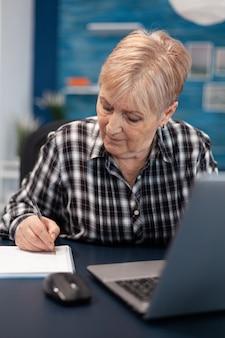 Volwassen ondernemer die notities maakt over een notebook die in een thuiskantoor werkt. oudere vrouw in huis woonkamer met behulp van moder technoloy laptop voor communicatie zittend aan een bureau binnenshuis.