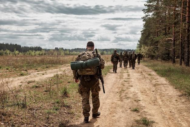 Volwassen oorlogsteamspellen met wapens, airsoft of strikeball, in het bos. groep soldaten in camouflage militaire uniformen met wapenkammen door gebied. militaire eenheid in bosuniform met geweer