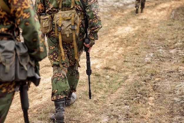 Volwassen oorlogsteamspellen met wapens, airsoft of strikeball, in het bos. groep soldaten in camouflage militaire uniformen met wapens kammen gebied. militaire eenheid in militair bosuniform met geweer
