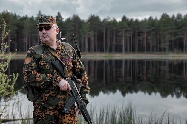 Volwassen oorlogsteamspellen met wapens, airsoft of strikeball, in het bos. leger soldaat in militair camouflage uniform met bril, wapen in handen. soldaat van middelbare leeftijd in bosuniform met autogun