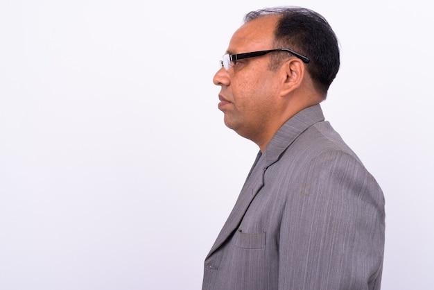 Volwassen overgewicht indiase zakenman in pak met teruglopende haarlijn op wit