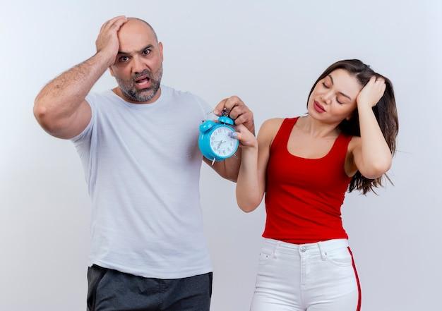 Volwassen paar angstige man op zoek en vermoeide vrouw met gesloten ogen, beide met wekker en hand op het hoofd