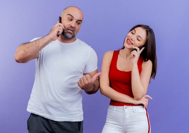 Volwassen paar beide praten aan de telefoon onder de indruk man kijken en wijzen naar vrouw en ze lacht en kijkt rechtdoor
