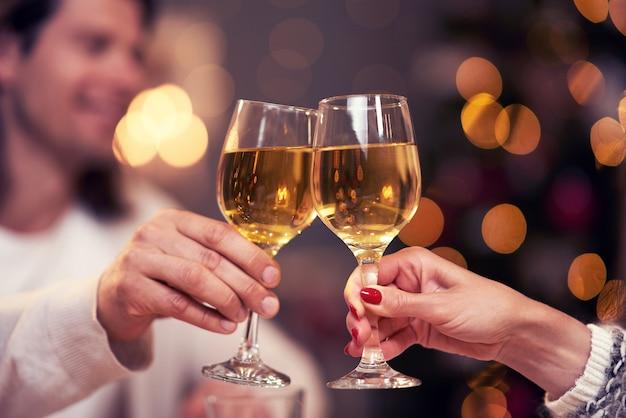 Volwassen paar dat wijn roostert op kerstachtergrond