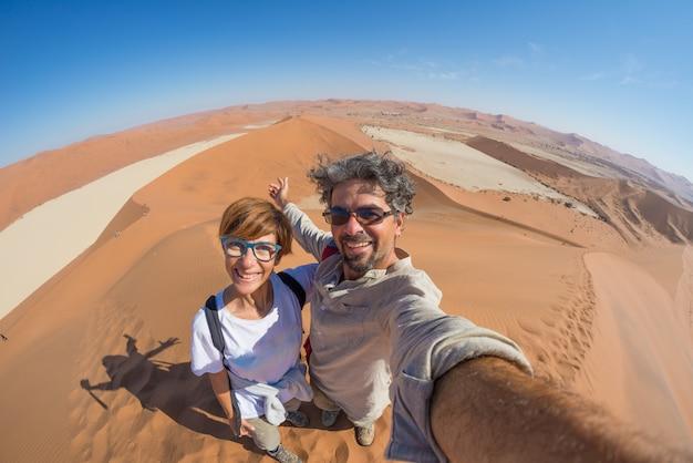 Volwassen paar die selfie op zandduinen in sossusvlei in de namib-woestijn nemen