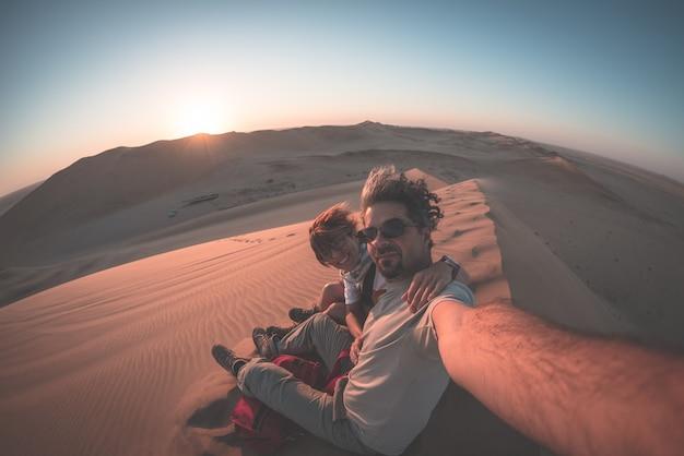 Volwassen paar die selfie op zandduinen nemen in de namib-woestijn