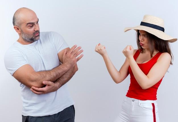 Volwassen paar fronsende vrouw die hoed draagt die boksgebaar doet en ontevreden man die zijn elleboog aanraakt en geen gebaar doet