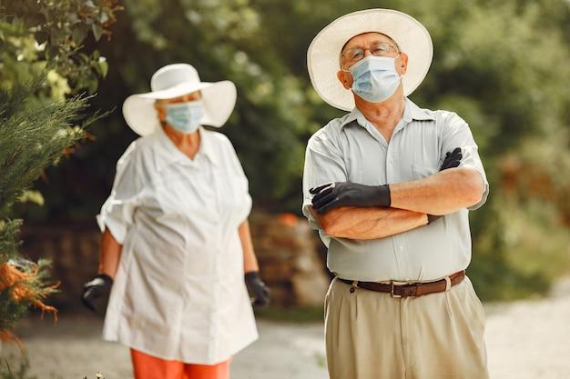 Volwassen paar in een zomertuin. coromavirus-thema. mensen met een medisch masker. knappe oudste in een wit overhemd.