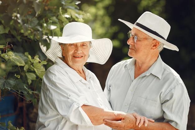 Volwassen paar in een zomertuin. knappe oudste in een wit overhemd. vrouw in een hoed.