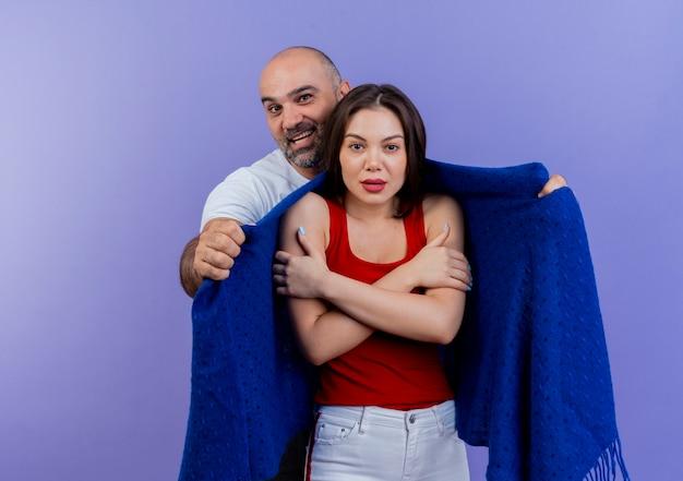 Volwassen paar onder de indruk man die koude vrouw bedekt met sjaal en ze houdt beide handen gekruist op zoek