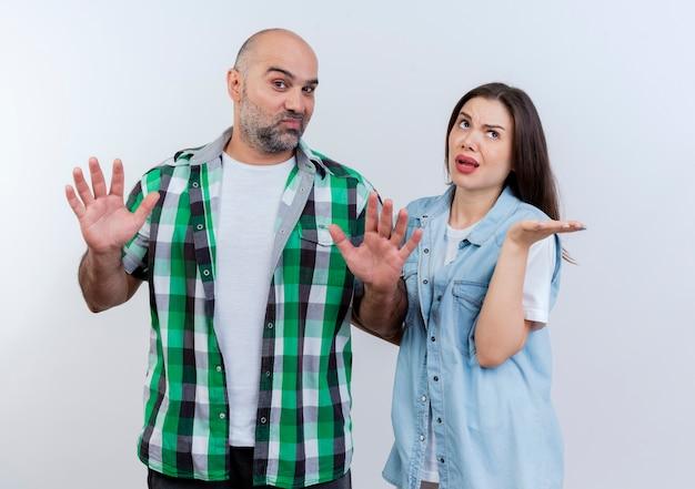 Volwassen paar onder de indruk man met lege handen kijken en clueless vrouw opzoeken met lege hand