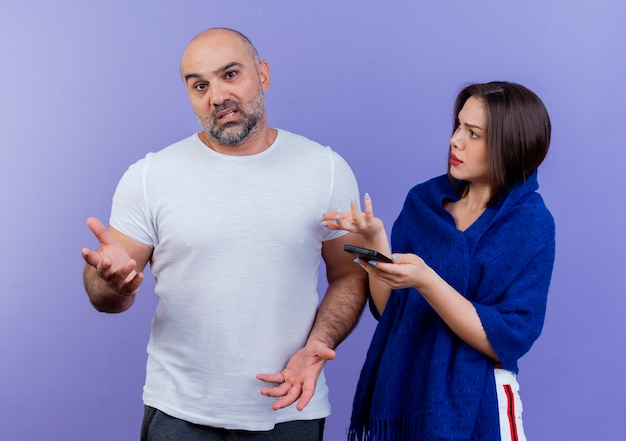Volwassen paar onder de indruk man met lege handen kijken onaangename vrouw gewikkeld in sjaal met mobiele telefoon met lege hand kijken naar de mens
