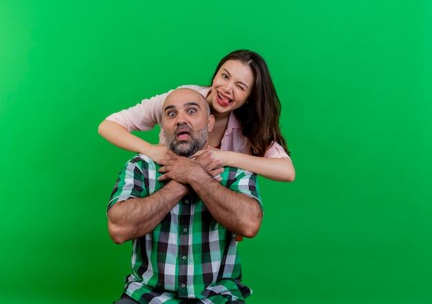 Volwassen paar speelse vrouw achter man verstikking hem tonen tong knipogen en onder de indruk man verstikking zichzelf beide kijken